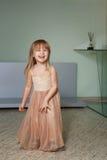 Маленькая девочка в красивом платье играет дома стоковые фотографии rf