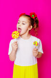 Маленькая девочка в красивом платье с большим леденцом на палочке конфеты Стоковое Фото