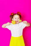 Маленькая девочка в красивом платье с большим леденцом на палочке конфеты Стоковая Фотография