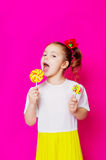 Маленькая девочка в красивом платье с большим леденцом на палочке конфеты Стоковое фото RF