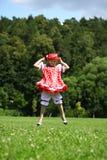 Маленькая девочка в красных sundress скача для утехи на лужайке Стоковое Фото