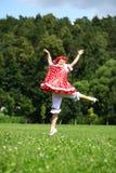 Маленькая девочка в красных sundress скача для утехи на лужайке Стоковые Фото
