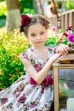 Маленькая девочка в красочных платье и цветках Стоковые Изображения