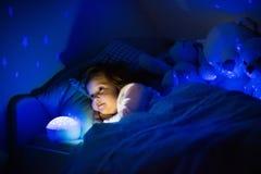 Маленькая девочка в кровати с лампой ночи стоковые фотографии rf