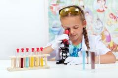 Маленькая девочка в классе науки используя микроскоп стоковые фотографии rf