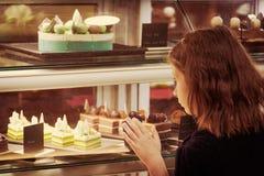 Маленькая девочка в магазине кондитерскаи смотря дисплей сладостно Стоковая Фотография RF