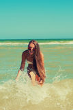 Маленькая девочка в морской воде брызгает и усмехаться Стоковое Изображение