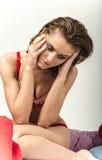 Маленькая девочка в нижнем белье в кровати плача и обтирая срывает мазать ее руки Стоковые Изображения