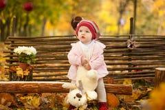 Маленькая девочка в парке осени сидя на деревянной скамье около загородки Стоковое Изображение