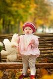 Маленькая девочка в парке осени сидя на деревянной скамье около загородки Стоковое Фото