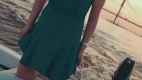 Маленькая девочка в пребывании платья бирюзы на коленях на моторной лодке Заход солнца романтично сток-видео