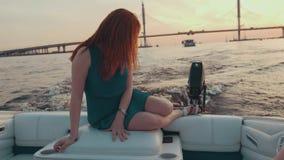 Маленькая девочка в платье бирюзы сидит на крае моторной лодки Заход солнца романтично видеоматериал