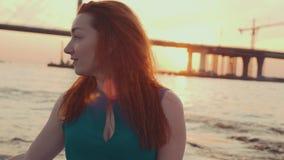 Маленькая девочка в платье бирюзы смотря unset на моторной лодке романтично Улыбка сток-видео