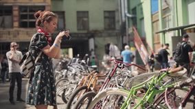 Маленькая девочка в платье принимает фото стойки велосипедов в линии на улице лето дня солнечное Встречать велосипедистов видеоматериал