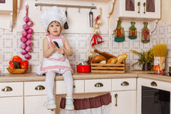 Маленькая девочка в рисберме в кухне Стоковые Изображения RF