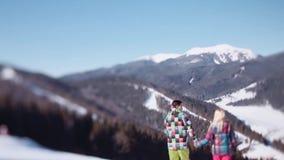Маленькая девочка в розовой носке лыжи и красивый молодой человек в зеленом костюме спорта зимы Симпатичная пара интересует вниз сток-видео