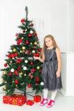Маленькая девочка в сером платье, стоя рядом с деревом Стоковое Фото