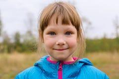Маленькая девочка в синем пиджаке outdoors Стоковое Изображение
