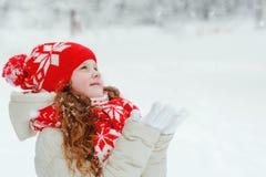 Маленькая девочка в снежинках красной крышки улавливая падая Стоковая Фотография RF