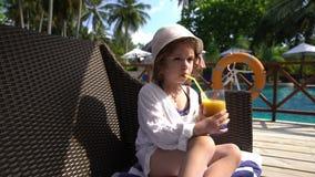 Маленькая девочка в соке соломенной шляпы выпивая бассейном сток-видео