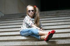 Маленькая девочка в солнечных очках сидя на лестницах Стоковое Изображение RF