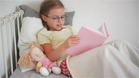 Маленькая девочка в стеклах читая книгу пока лежащ в кровати Рядом с ей сидит кукла видеоматериал
