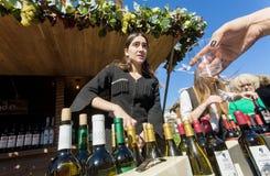 Маленькая девочка в традиционном грузинском платье льет вино для посетителей фестиваля Стоковые Изображения