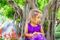 Маленькая девочка в тропическом саде вал сосенки бонзаев вечнозеленый миниатюрный Стоковое фото RF