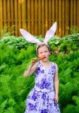 Маленькая девочка в ушах зайчика принимая укус моркови Стоковая Фотография