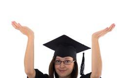 Маленькая девочка в хламиде студента показывает руку Стоковое Изображение