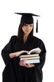 Маленькая девочка в хламиде студента с стогом книг Стоковые Изображения