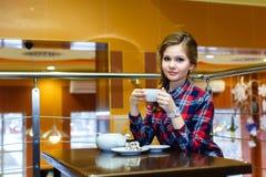 Маленькая девочка в чае рубашки шотландки выпивая в кафе Стоковая Фотография
