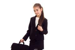 Маленькая девочка в черной куртке держа дипломата Стоковая Фотография
