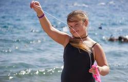 Маленькая девочка в черном купальнике стоя в море Стоковые Изображения RF
