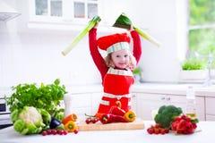 Маленькая девочка в шляпе шеф-повара подготавливая обед Стоковое Изображение RF