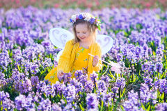 Маленькая девочка в fairy костюме играя в поле цветка Стоковое Фото