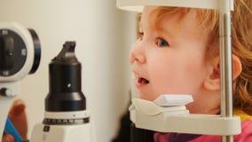 Маленькая девочка в ophthalmological клинике проверяет зрение Стоковое Фото
