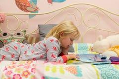 Маленькая девочка в ` s PJ читая Storybook в кровати Стоковые Изображения RF