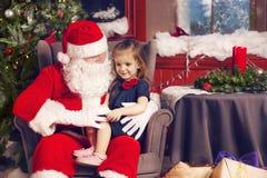 Маленькая девочка говоря ей желание рождества в Санта Клаусе Стоковое фото RF