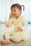Маленькая девочка говоря на мобильном телефоне Стоковое фото RF