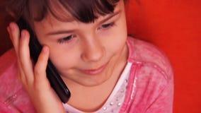 Маленькая девочка говоря на мобильном телефоне видеоматериал