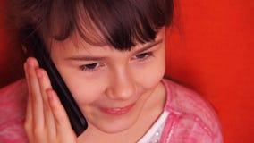 Маленькая девочка говоря на мобильном телефоне акции видеоматериалы