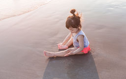 Маленькая девочка 2-3 года игр на пляже в заходе солнца Стоковые Изображения