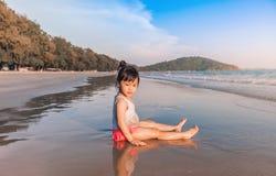 Маленькая девочка 2-3 года игр на пляже в заходе солнца Стоковые Фотографии RF