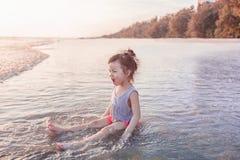 Маленькая девочка 2-3 года игр на пляже в заходе солнца Стоковые Изображения RF