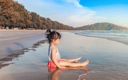 Маленькая девочка 2-3 года игр на пляже в заходе солнца Стоковые Фото