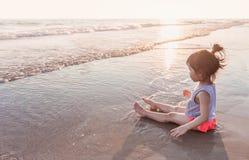Маленькая девочка 2-3 года игр на пляже в заходе солнца Стоковое Изображение RF