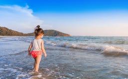 Маленькая девочка 2-3 года игр на пляже в заходе солнца Стоковое Изображение