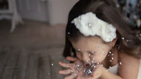 Маленькая девочка 3 года дуя на серебряных sequins видеоматериал