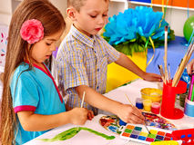 Маленькая девочка группы с картиной щетки в детском саде Стоковое фото RF
